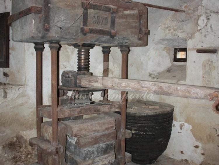 Prensa de aceite en estancia de la planta baja de la masía