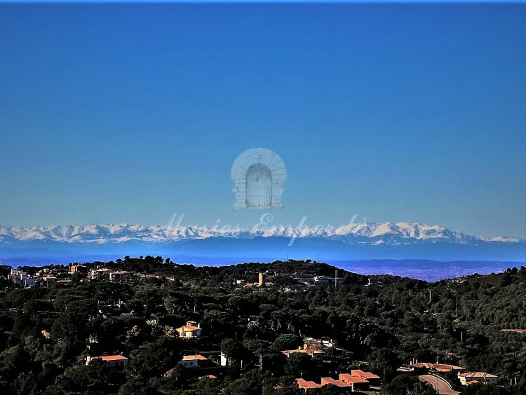 View of the parcel of Begur and the Pyrenees at the bottom of the image