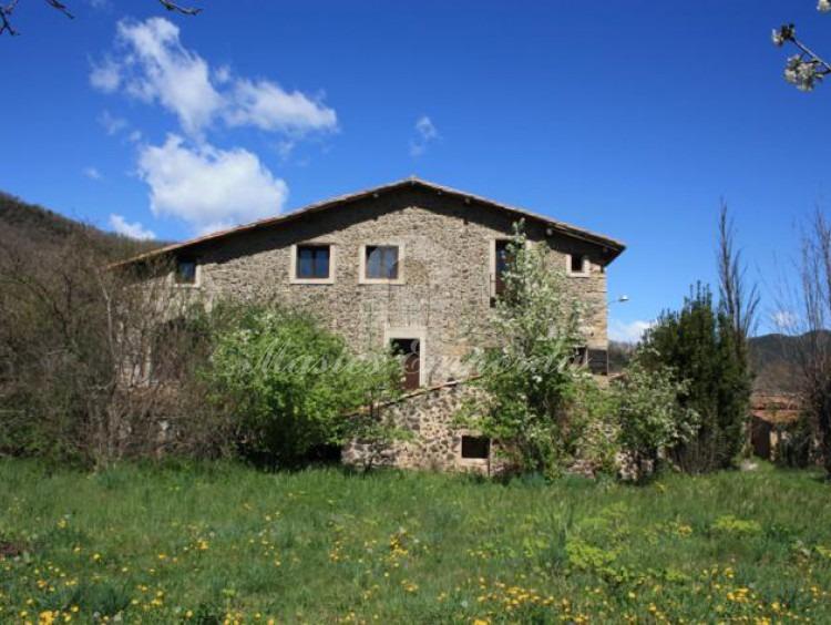 Fachada lateral de la masía y jardín y parte del huerto de la propiedad