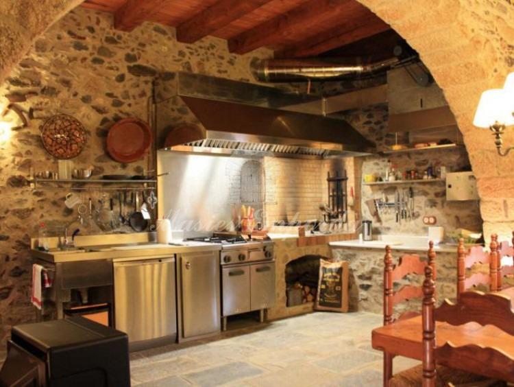Gran salón de comedor y cocina de la planta baja junto a la bodega de la casa