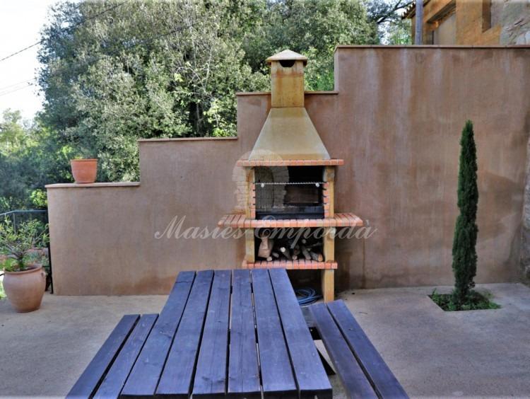 Detalle de la barbacoa y la mesa de la terraza