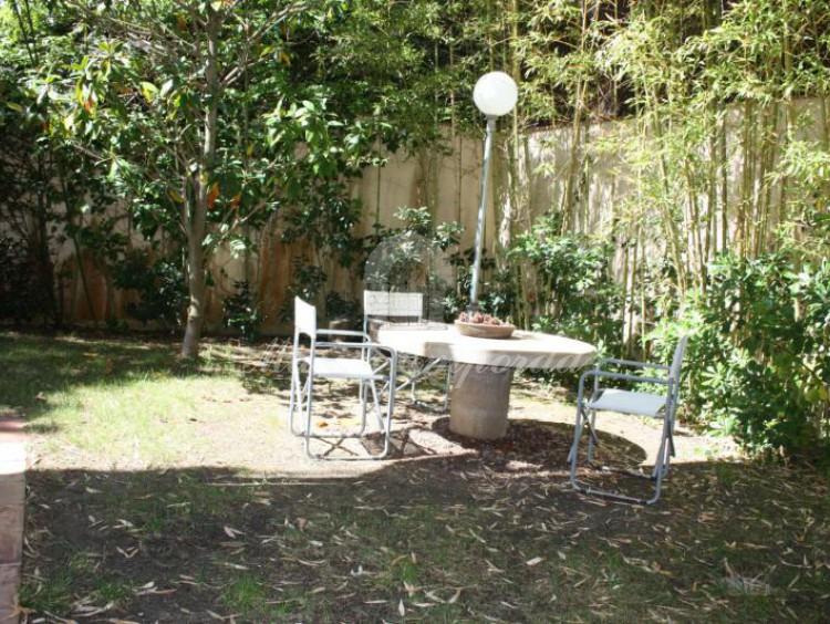 Desde otro ángulo la zona del jardín donde se encuentra la barbacoa y el comedor de verano junto a la cocina