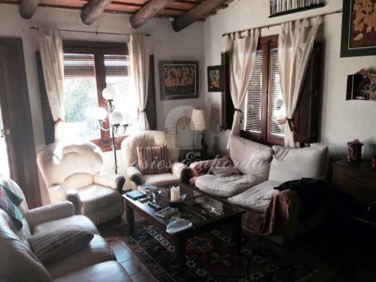 Salón de estar de la planta con chimenea y acceso directo al jardín