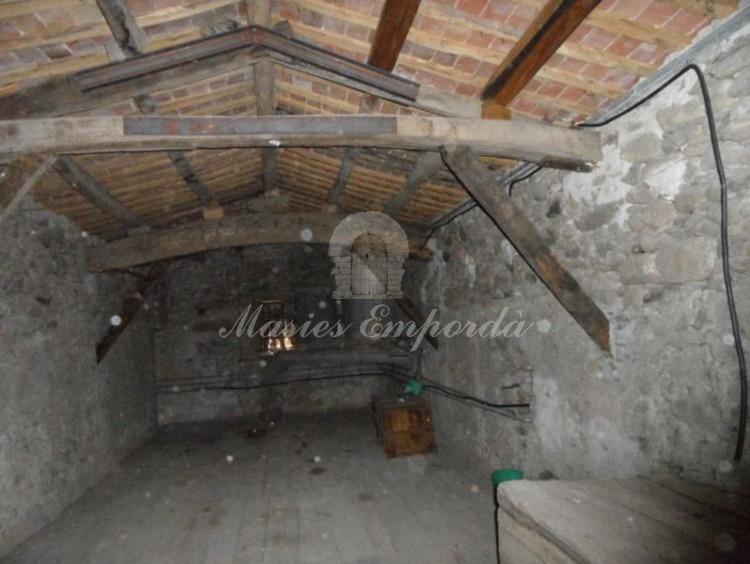 Salón de segunda planta con cubierta a dos aguas con vigas vistas de madera